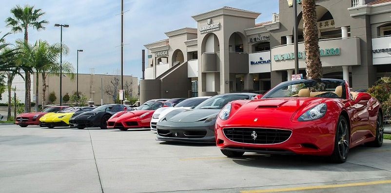 A line of supercars at a meetup.